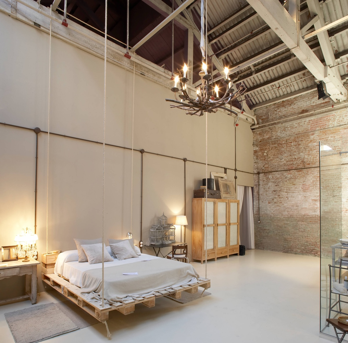 barn-style-with-chandelier-exposed-brick-bedroom